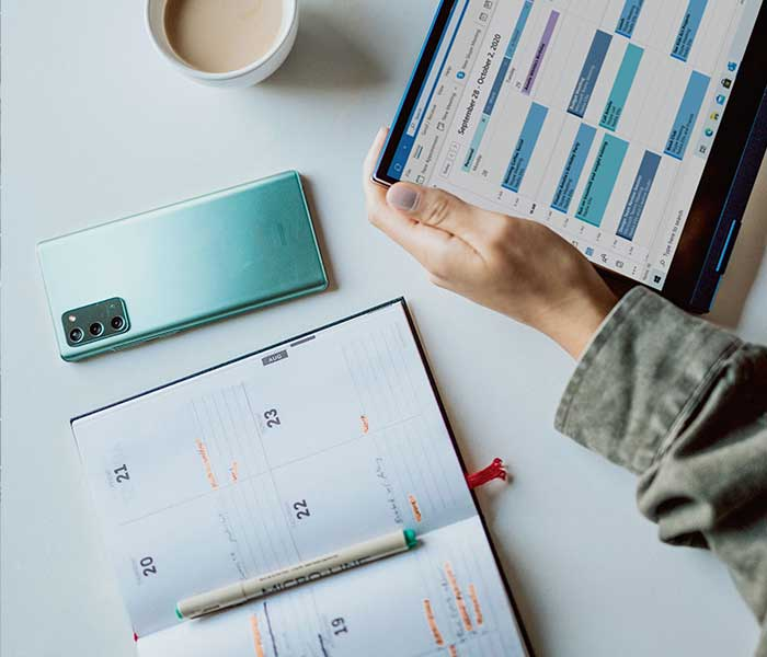 Person looking at their calendar on their tablet | Axiomatics