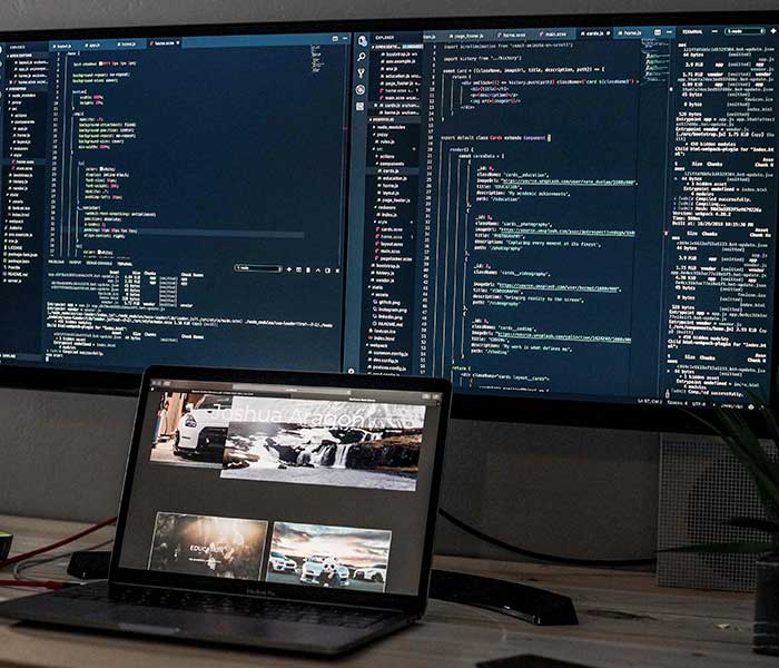 Laptop sitting in front of a large screen with two code windows opened | Axiomatics